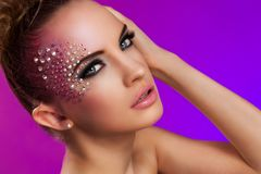 Beautiful woman with fantasy makeup. On a violet background Royalty Free Stock Image