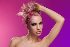 Beautiful woman with fantasy makeup. On a violet background Royalty Free Stock Photography