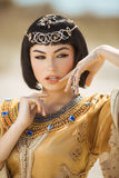 Beautiful woman with fashion make-up and hairstyle like Egyptian queen Cleopatra outdoors against desert royalty free stock photo