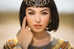 Beautiful woman with fashion make-up and hairstyle like Egyptian queen Cleopatra outdoors against desert Stock Photography