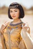 Beautiful woman with fashion make-up and hairstyle like Egyptian queen Cleopatra outdoors against desert Royalty Free Stock Images