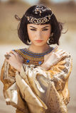 Beautiful woman with fashion make-up and hairstyle like Egyptian queen Cleopatra outdoors against desert windy weather royalty free stock image