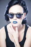Beautiful woman fashion model portrait in sunglasses with blue lips and earrings. Creative hairstyle and make up Stock Photography