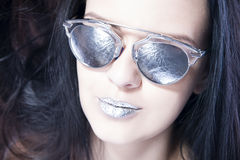 Beautiful woman fashion model portrait in sunglasses with metallic silver lips. Creative hairstyle and make up Royalty Free Stock Photos