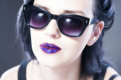 Beautiful woman fashion model portrait in sunglasses with red and blue lips. Creative hairstyle and make up Stock Photography