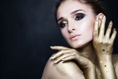 Beautiful Woman Fashion Model with Smoky Eyes Makeup. With Gold and Black Eyeshadow on Background with Copy space royalty free stock photos