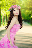 Beautiful Woman Fashion Model wearing Prom Dress. With Flowers on Green Blurred Background Outdoors royalty free stock photography