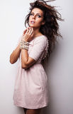 Beautiful woman on fashionable dress pose in studio. Royalty Free Stock Image