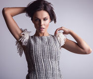 Beautiful woman on fashionable dress pose in studio. Royalty Free Stock Images