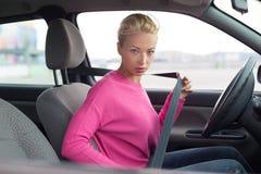 Beautiful woman fastening seat belt. Stock Photo