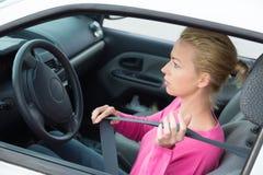 Beautiful woman fastening seat belt. Royalty Free Stock Image