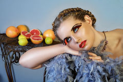Beautiful woman with feathers and fruit Stock Images