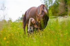 Beautiful woman feeding her arabian horse in the field Royalty Free Stock Photo