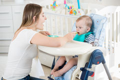 Beautiful woman feeding her baby boy in highchair at living room Stock Image