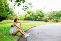 Beautiful woman feel tried and thirsty because it's sunny day. Charming beautiful girl take a rest and feel relaxed, happy while royalty free stock photos