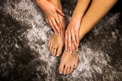 Beautiful woman feet and hands with french manicure and pedicure natural nail design, fingers with long nails touching soft skin stock image