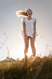 Beautiful woman in a field being carefree. Royalty Free Stock Photography