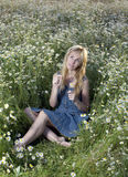 Beautiful woman in the field of camomiles and guesses on a camomile Stock Photography