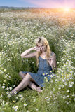 Beautiful woman in the field of camomiles and guesses on a camomile Stock Image