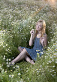 Beautiful woman in the field of camomiles guesses on a camomile Royalty Free Stock Photography
