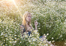 Beautiful woman in the field of camomiles guesses on a camomile Royalty Free Stock Image