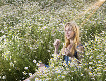 Beautiful woman in the field of camomiles guesses on a camomile Stock Photo