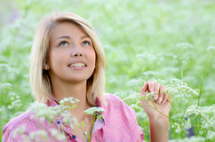 The beautiful woman in the field with flower Royalty Free Stock Photo
