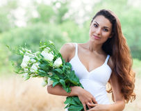 Beautiful woman in field with flowers Royalty Free Stock Photography