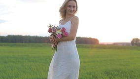 Beautiful woman in field with flowers at sunset.  stock footage