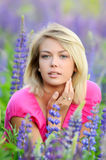 The beautiful woman in the field with lupin Royalty Free Stock Image