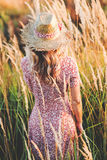 Beautiful woman in field at summer sunset backview Royalty Free Stock Images