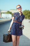 Beautiful woman in fifties style with braces holding retro camer Stock Photos