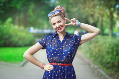 Beautiful woman in fifties style with braces winking. Beautiful young woman in fifties style with braces winking outdoor Royalty Free Stock Photography