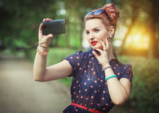 Beautiful woman in fifties style taking picture of herself. Beautiful young woman in fifties style taking picture of herself outdoor Stock Images