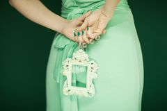 Beautiful woman figure, bridesmaid in light green dress holding vintage frame stock photography