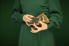 Beautiful woman figure in dark green 50`s dress holding vintage book. Hands with green nail polish Stock Photos