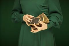Beautiful woman figure in dark green 50`s dress holding vintage book stock photos