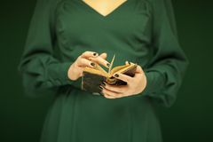 Beautiful woman figure in dark green 50`s dress holding vintage book. Hands with green nail polish Royalty Free Stock Photo