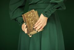 Beautiful woman figure in dark green 50`s dress holding vintage book. Hands with green nail polish Royalty Free Stock Photography
