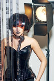 Beautiful woman with filmstrips hairstyle. Beautiful stylish woman with film hairstyle in leather corset posing in studio with filmstrip rolls Royalty Free Stock Images