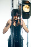 Beautiful woman with filmstrips hairstyle. Beautiful stylish woman with film hairstyle in leather corset posing in studio with filmstrip rolls Stock Images