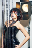 Beautiful woman with filmstrips hairstyle. Beautiful stylish woman with film hairstyle in leather corset posing in studio with filmstrip rolls Royalty Free Stock Photography