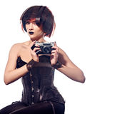 Beautiful woman with filmstrips hairstyle. Beautiful stylish woman in leather corset with film Hairstyle holding retro camera and hands tying with filmstrip roll Royalty Free Stock Photography