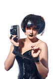 Beautiful woman with filmstrips hairstyle. Beautiful stylish woman in leather corset with film Hairstyle holding retro camera and hands tying with filmstrip roll Royalty Free Stock Image