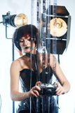 Beautiful woman with filmstrips hairstyle. Beautiful stylish woman in leather corset and filmstrip hairstyle with film strips posing in studio with retro camera Royalty Free Stock Image