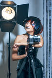 Beautiful woman with filmstrips hairstyle. Beautiful stylish woman in leather corset and filmstrip hairstyle with film strips posing in studio with retro camera Stock Photography