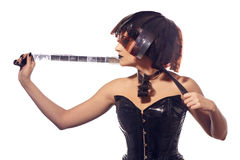 Beautiful woman with filmstrips hairstyle. Beautiful stylish woman in leather corset and filmstrips hairstyle posing isolated on white background Royalty Free Stock Image