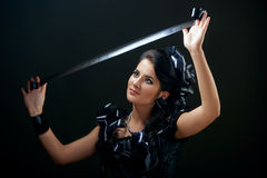 Beautiful woman with filmstrips hairstyle. Beautiful young brunette woman in a black dress decorated with camera rolls Royalty Free Stock Photography