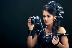 Beautiful woman with filmstrips hairstyle. Beautiful young brunette woman in a black dress decorated with camera rolls holding retro camera Stock Photo