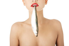 Beautiful woman with fish in her mouth Stock Images